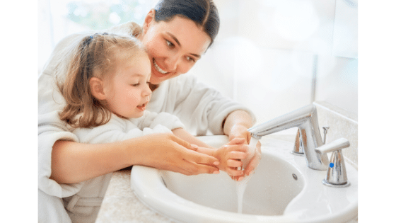 Lady and young girl washing hands